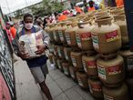 """BRA01. RIO DE JANEIRO (BRASIL), 29/04/21.- Un hombre lleva uno de los paquetes con alimentos que fueron entregados a un grupo de personas que compró gas a mitad de precio durante una campaña promovida por una federación de trabajadores en Río de Janeiro. La Federación Unitaria de Trabajadores Petroleros, con motivo de la campaña """"Combustible a precio Justo """" vende cilindros de gas para cocinar por menos de la mitad del valor que cobran los distribuidores en todo el país, además repartirá alimentos y mascarillas de protección contra la covid-19. EFE/Antonio Lacerda"""