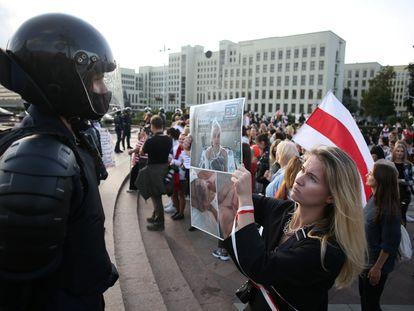 Uma mulher segura uma foto em frente a um policial de uma pessoa torturada durante protesto em Minsk neste sábado.