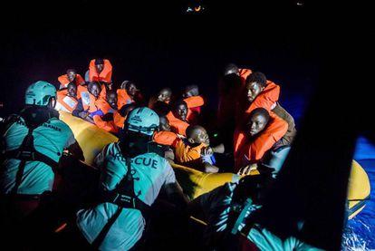Membros de SOS Mediterranée resgatam migrantes na noite deste sábado.