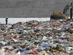 An environmental worker stands near an excavator amid waste at Tianziling landfill in Hangzhou, Zhejiang province, China August 7, 2019. Picture taken August 7, 2019. REUTERS/Stringer  ATTENTION EDITORS - THIS IMAGE WAS PROVIDED BY A THIRD PARTY. CHINA OUT. - RC16566D9530
