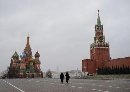 Dois policiais caminham pela praça Vermelha de Moscou, em frente à catedral de São Basílio, e o Kremlin, nesta segunda-feira, primeiro dia de quarentena na capital russa.