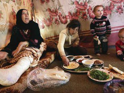 Uma mulher síria almoça com seus filhos em campo de refugiados de Saadnayel.