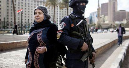 Uma mulher passa ao lado de um soldado, próximo à praça Tahrir.
