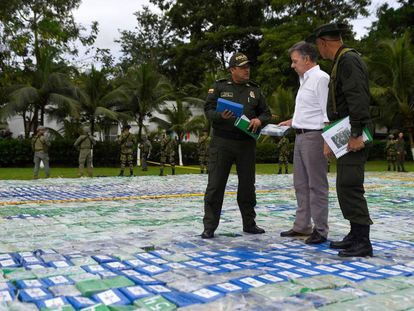 O presidente da Colômbia, Juan Manuel Santos, e dois agentes sobre as mais de 12 toneladas de cocaína apreendida