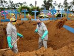 TOPSHOT - Brazilian Ulisses Xavier, 52, who has worked for 16 years at Nossa Senhora cemetery in Manaus, Brazil, digs a grave alongside a co-worker during their shift on May 8, 2020, amid the new coronavirus pandemic. - Xavier works 12 hours a day and supplements his income by making wooden crosses for graves. The cemetery has seen a surge in the number of new graves after the outbreak of COVID-19. (Photo by MICHAEL DANTAS / AFP)