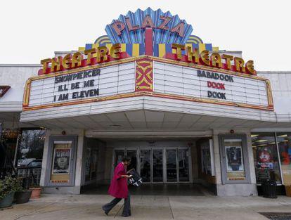 Mulher diante do cinema em Atlanta que anunciou que projetará o filme.