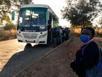 Passengers wearing face masks line up to board a government subsidised bus for transport to work in Harare on May 6, 2020. - The Zimbabwe government has made it mandatory for people to wear face masks in public during the COVID-19 coronavirus lockdown. (Photo by Jekesai NJIKIZANA / AFP)