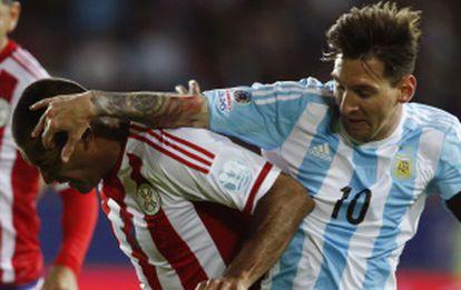 Messi disputa a bola com o paraguaio Da Silva.