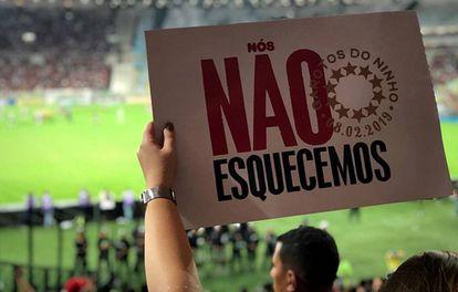 Torcedores do Flamengo mostram cartaz no estádio em referência ao incêndio.