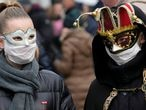Masked carnival revellers wear protective face masks at Venice Carnival, which the last two days of, as well as Sunday night's festivities, have been cancelled because of an outbreak of coronavirus, in Venice, Italy February 23, 2020.  REUTERS/Manuel Silvestri