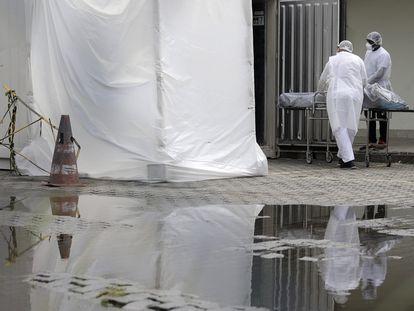 Profissionais de saúde vestindo equipamentos de proteção transportam o corpo de uma pessoa no Rio de Janeiro, em maio.