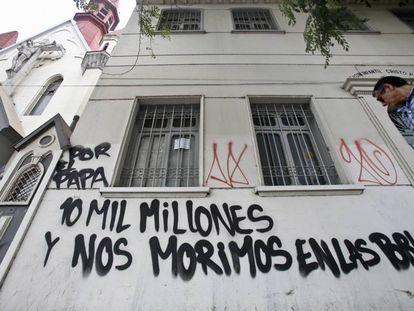 """Pichação numa igreja: """"10 bilhões pelo Papa enquanto o povo morre nas comunidades""""."""