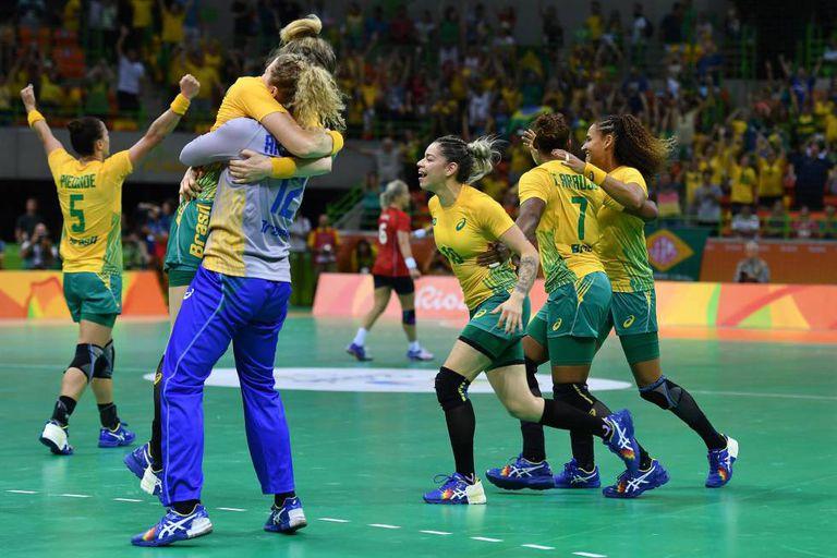 A equipe feminina de handebol comemora a vitória.