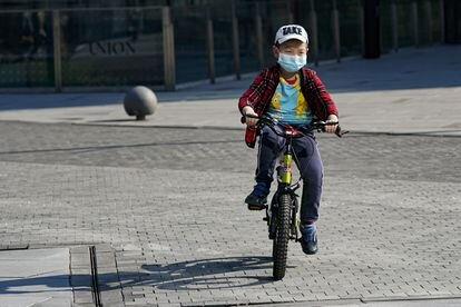 Menino anda de bicicleta com uma máscara em Pequim.