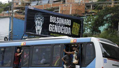 Passageiros circulam em ônibus lotado nesta terça-feira, no Rio de Janeiro, ao lado de outdoor crítico a Jair Bolsonaro.