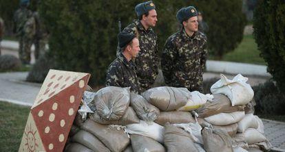 Soldados ucranianos se protegem atrás de sacos de terra na base de Belbek, próximo a Sebastopol.