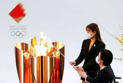 A atriz Satomi Ishihara e o atleta paralímpico Aki Taguchi acendem a pira olímpica em Nahara (Fukushima) em 25 de março.