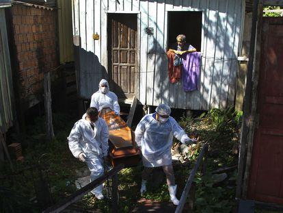 Funcionários municipais recolhem o corpo de uma nonagenária que morreu por complicações da covid-19 em sua casa em Manaus na última sexta-feira.