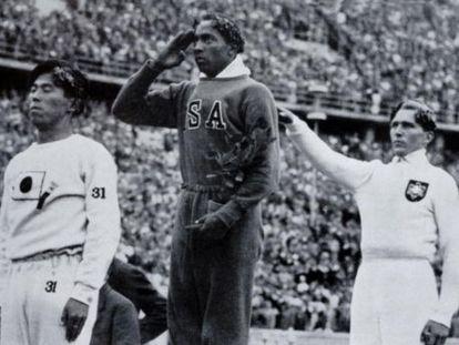 Jesse Owens no pódio olímpico depois de sua vitória no salto em distância nos Jogos Olímpicos de Berlim 1936.