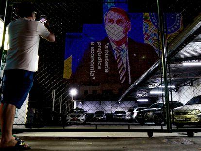 """Um imagem do presidente Jair Bolsonaro com a frase """"a histeria prejudica a economia"""" é projetada em prédio de São Paulo."""