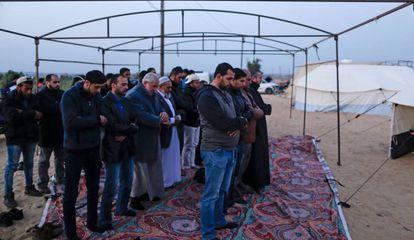 Grupo de muçulmanos palestinos no momento da oração, enquanto montam uma barraca na Faixa de Gaza em 29 de março de 2018