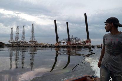 Pescador observa uma velha infraestrutura no lago Maracaibo, na Venezuela.