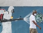 A man walks next to a graffiti depciting a cleaner wearing protective gear spraying viruses with the face of Brazil's President Jair Bolsonaro amid the coronavirus disease (COVID-19) outbreak, in Rio de Janeiro, Brazil, June 12, 2020. REUTERS/Sergio Moraes
