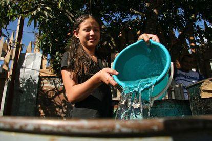 Menina enche um recipiente com água em Honduras.