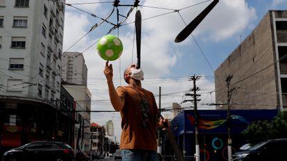 Homem faz malabares em rua de São Paulo no início de março.