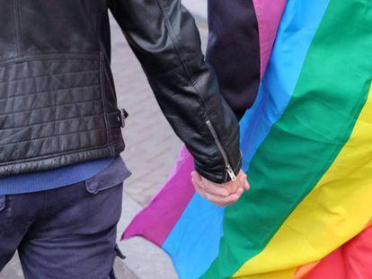 Casal de mãos dadas diante da bandeira multicolorida que identifica a causa LGBTI.