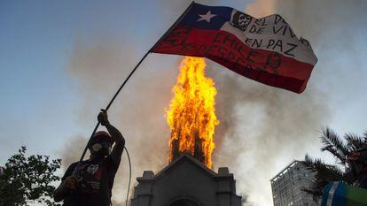 Manifestante balança bandeira chilena diante de igreja incendiada em Santiago, neste domingo.