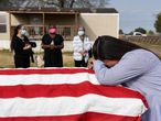 "Lila Blanks reacts next to the casket of her husband, Gregory Blanks, 50, who died from complications from the coronavirus disease (COVID-19), ahead of his funeral in San Felipe, Texas, U.S., January 26, 2021. Blanks ran a heating and air conditioning business in the Houston area. He was a huge fan of the Dallas Cowboys football team. In keeping with current restrictions to prevent infections, only a limited number of family and friends were able to attend the burial at San Felipe Community Cemetery. Clad in a face mask sporting the logo of her husband's company, Blanks' wife Lila solemnly watched as some of Pryor's workers lowered the casket into the ground. ""We need to all do what we need to do to get over it,"" she said. ""So it'll be over and we don't keep burying our husbands, our children, our mothers, our fathers."" REUTERS/Callaghan O'Hare     SEARCH ""FUNERALS O'HARE"" FOR THIS STORY. SEARCH ""WIDER IMAGE"" FOR ALL STORIES"