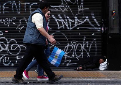 Mulher dorme na calçada enquanto pessoas caminham durante a celebração do bicentenário da independência argentina, em Buenos Aires.