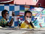 BRA50. SAO PAULO (BRASIL), 28/05/2020.- Un hombre camina frente a un grafiti con la imagen de los jugadores de fútbol de Brasil, Paulinho y Marta, realizado por el artista Rodrigo Rodrigues, conocido como Digãocomprimido, que pone máscaras en algunas de sus obras callejeras para crear conciencia sobre el coronavirus en Brasilandia, un barrio en la periferia de la ciudad con el mayor número de muertes por covid-19 hoy, jueves en Sao Paulo. EFE/Sebastião Moreira