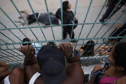 Pessoas olham para o corpo de um dos homens executados pela polícia do Rio, em 30 de março.