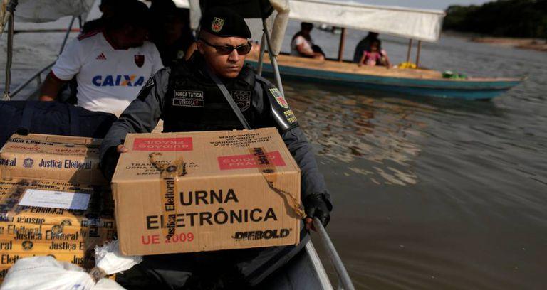 Policial carrega urna eletrônica no Rio Negro, em Manaus.