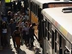 Commuters board a bus in Rio de Janeiro, Brazil, Monday, March 16, 2020. (AP Photo/Silvia Izquierdo)