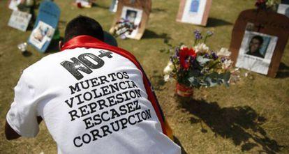 Cidadão diante de túmulos de vítimas da criminalidade na Venezuela.