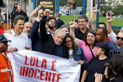 O ex-presidente Lula ao deixar a prisão em Curitiba, abraçado pela namorada e por apoiadores.