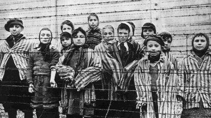 Um grupo de crianças atrás da cerca do campo nazista de Auschwitz.