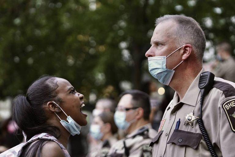 Mulher repreende policial durante os protestos em Minneapolis.