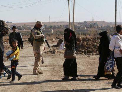 Soldados iraquianos evacuam civis durante os confrontos com membros do Estado Islâmico a sudoeste de Mossul.