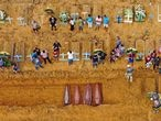 (FILES) This file aerial picture taken on April 22, 2020 shows a burial taking place at an area where new graves have been dug up at the Nossa Senhora Aparecida cemetery in Manaus, in the Amazon forest in Brazil, during the COVID-19 coronavirus pandemic. - Brazil's COVID-19 death toll passed 15,000 on May 16, 2020, official figures showed, while its number of infections topped 230,000, making it the country with the fifth highest number of cases in the world. (Photo by Michael DANTAS / AFP)