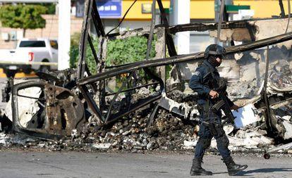 Um policial em frente a um veículo queimado nesta sexta-feira em Culiacán.