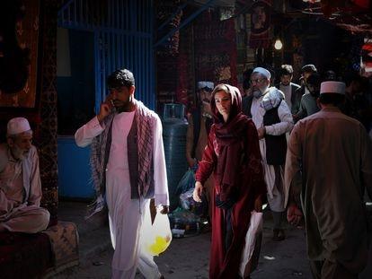Uma mulher caminha entre homens pelas ruas do bazar Mandawi, em Cabul.