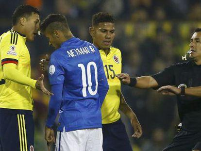 Neymar encara o colombiano Murillo, e o árbitro Enrique Osses tenta impedi-lo.