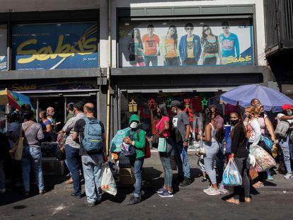 Grupo de passageiros espera em ponto de ônibus em Caracas, em 30 de dezembro.