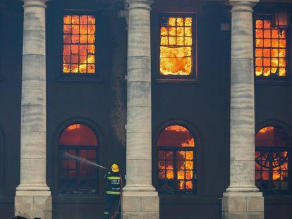Bombeiro combate o incêndio que destruiu a Biblioteca Jagger, de quase 200 anos, no campus da Universidade da Cidade do Cabo (UCT), na África do Sul, no domingo.