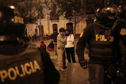 Um casal escuta as notícias na noite eleitoral em uma rua de Lima, neste domingo.