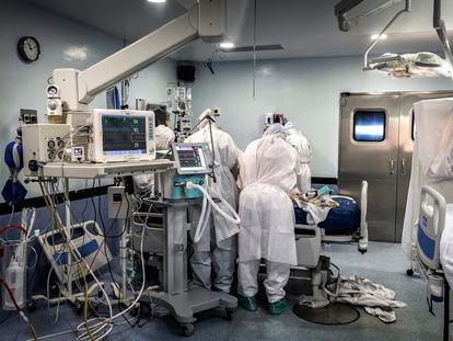Trabalhadores da saúde atendem um paciente internado com covid-19 em um hospital da Espanha.